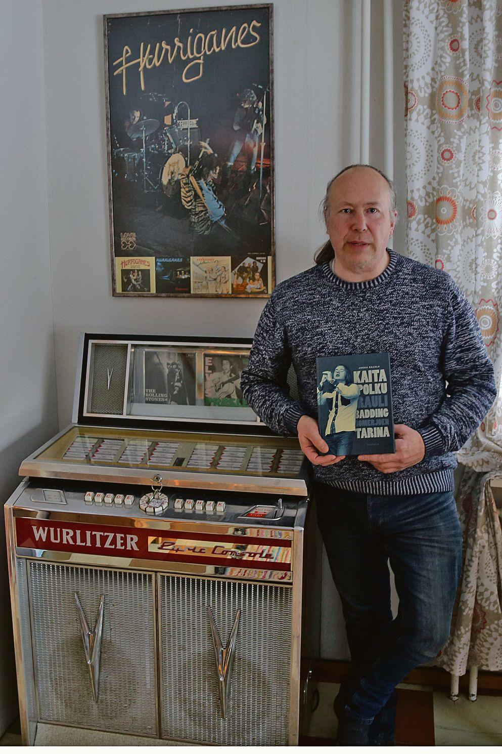 Jukka Rajala kädessään Rauli Badding Somerjoen elämänkerta Kaita polku, ja vieressään oma jukeboxi, jonka mallinen löytyy sattumoisin myös Baddingin Muotokuva 1 -LP:n kannesta.